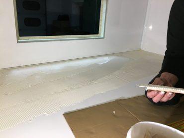 Beim Auftragen des Klebers für Holzplatte auf dem Bett