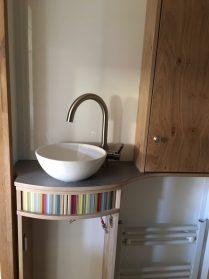 Unser Bad: Ober- und Unterschrank (mit farbiger Resopaleinlage), aufgesetztes Waschbecken, kleiner Heizkörper unten rechts