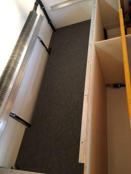 Stauraum unter der Sitzgruppe: mit Rippenfilz bezogene Platte, die als Regal dienen soll; Heizelement links