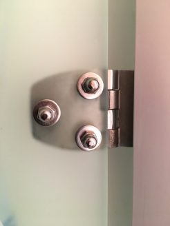Unsere Duschtür aus Plexiglas mit Edelstahl-Scharnieren und Hutmuttern zur Befestigung