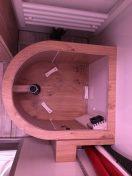 Trenntoilette von innen: Ventilator rechts unten, Holzklötzchen in der Mitte zur Stabilisierung des Eimers, links das Rohr zum Urintank