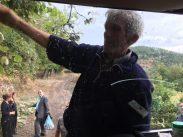 Dorfbewohner hält Ast während Akin ihn absägt; außerdem versammeln sich immer mehr Menschen