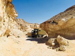 Der Benz schnuppert sich den Weg um die Kalkfelsen im Oman