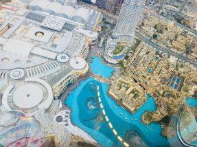 Blick vom 123. Stock des Burj Khalifa auf die Dubai Mall (links) und die Dubai Fountain, die gerade loslegt