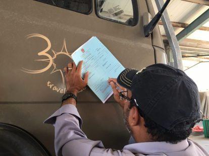Vorbereitung der Verschiffung nach Bandar Abbas: Aufkleber (oben) ist drauf und die Abmessungen vom Benz werden notiert.