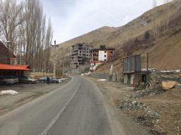 Auf dem Weg zum Skigebiet Dizin: viele Bauruinen, die bereits wieder zerfallen. Vorne rechts ein Skiverleih
