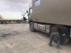 Auf dem Pamir Highway: Alex löst mit geliehenem LKW-Werkzeug die Radmuttern...