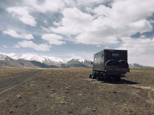 Reparatur am Pamir Highway: unser linker Luftfederbalg ist durchgescheuert und Alex muss bei kalten Temperaturen und Wind tauschen