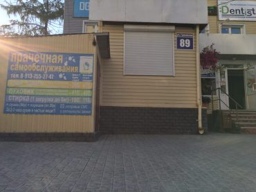Wäscherei in Novosibirsk; durch die offene Tür durch und nach hinten laufen; vorne links die Preise vormittags und nachmittags und pro große bzw kleine Maschine