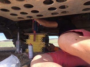 Alex stützt den Antriebsstrang mittels Wagenheber und Spanngurten