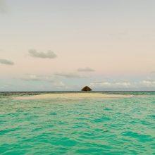 Eine kleine Insel mit viel Sand und einer Palapa